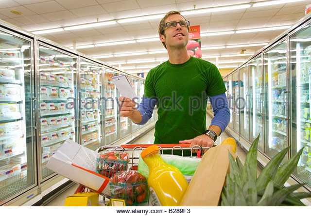 Man grocery shopping in frozen foods section - Stock Image