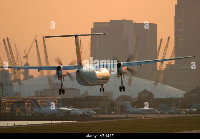 British European Dash 8 landing at London City airport with Millenium Dome in the background 2004 - Stock Image