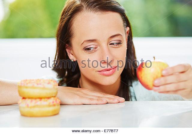 Woman deciding between fruit and a doughnut - Stock Image