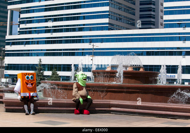 Performers dressed as famous children's television characters wait for customers on a fountain in front of Water - Stock Image