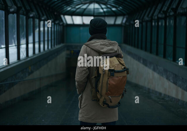 Man standing in tunnel carrying backpack - Stock Image