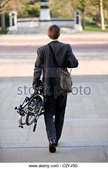 A businessman carrying his folded bicycle to work - Stock Image