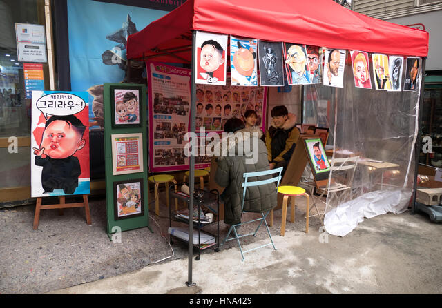 Man painting caricatures. Stall selling paintings of celebrities. Seoul, South Korea, Asia - Stock Image