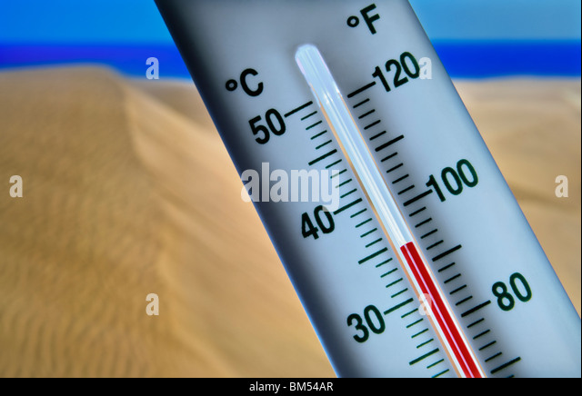 Thermometer displays 34 degrees centigrade against hot dry and sunny  coastal sand dunes sea and blue sky - Stock Image