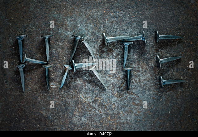 The word 'HATE' written with studs on a metal background - Stock Image