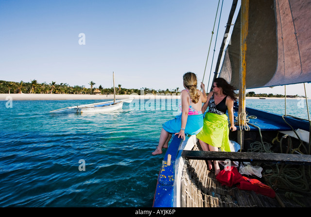 Tourists enjoy the tranquil setting and sailing on a dhow  A traditional sailing boat of the region Benguerra Lodge - Stock Image
