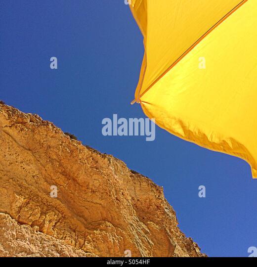 Yellow parasol, blue sky and rocks, Algarve, Portugal - Stock Image