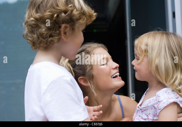 Mother bonding with two young children - Stock Image