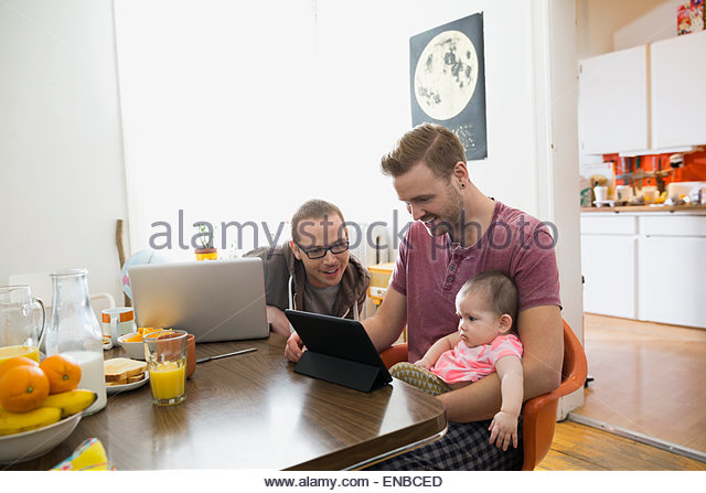 Homosexual couple using technology with baby daughter table - Stock Image