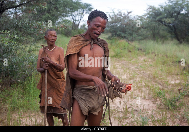 Elderly woman and Bushman / San showing roots and in the Kalahari desert near Ghanzi, Botswana, Africa - Stock Image