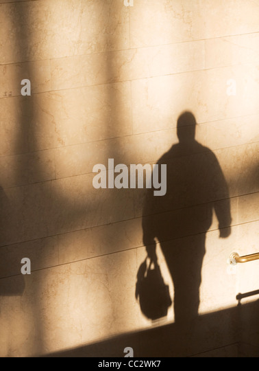 USA, New York City, Shadow of male pedestrian on sunlit wall - Stock Image
