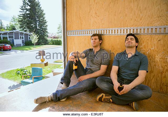 Men drinking beer and resting inside moving van - Stock Image