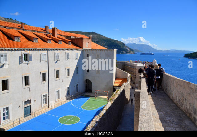 Tourists walk along the wall of the walled city of Dubrovnik, Croatia, passing a netball court belonging to a local - Stock Image
