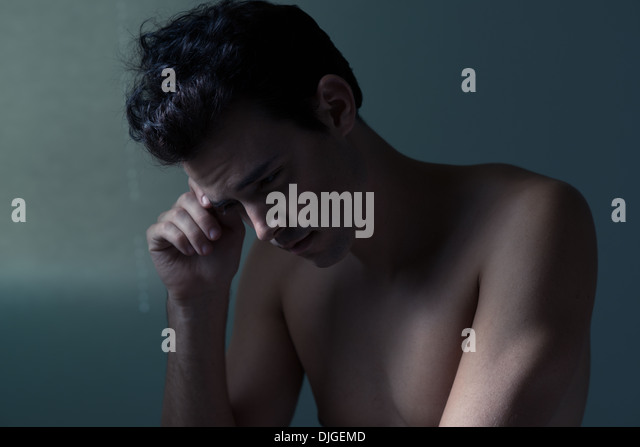 handsome dark hair Caucasian young man doubting himself, thinking, questioning life. He is emotional, a moody portrait - Stock Image