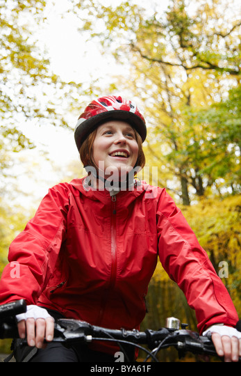 Happy girl cycling surrounded by trees - Stock Image