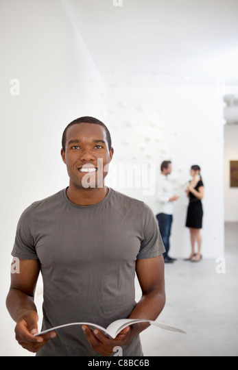Front view of young man in casual looking up - Stock Image