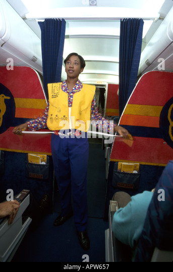 St. Lucia West Indies airport Air Jamaica Black flight attendant demonstrates inflatable life vest - Stock Image
