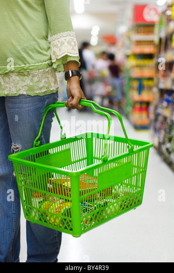 shopping in supermarket, carrying a grocery basket - Stock Image