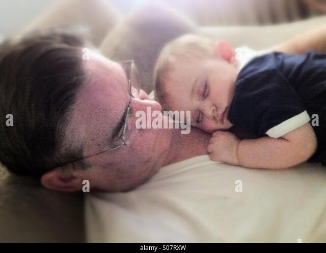 Soft image of granddad with baby boy sleeping on his chest. - Stock Image