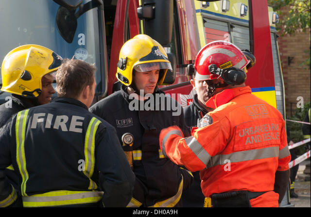 Hounslow, London, UK. 28th October 2013. An Urban Search and Rescue (USAR) crew member talks to London Fire Brigade - Stock Image