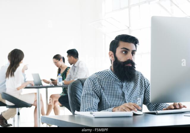 Business people working on computer at office - Stock Image