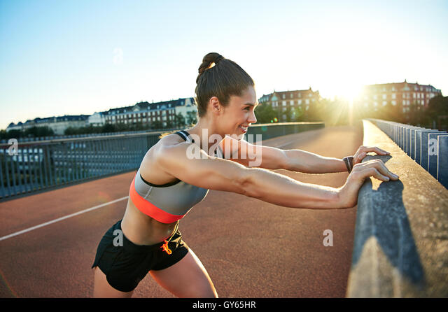 Smiling muscular jogger presses against railing as she stretches her legs before running - Stock Image