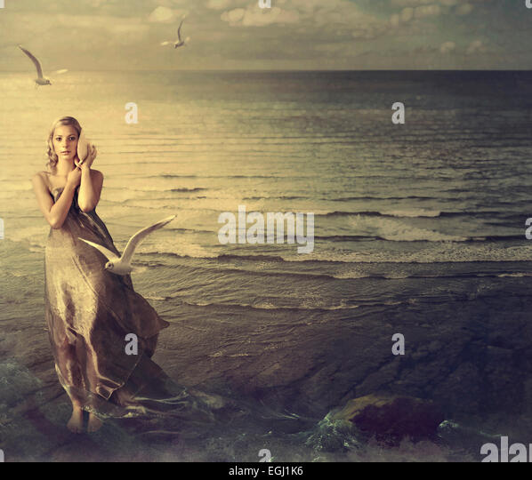 young woman holding a shell by the ocean - Stock Image