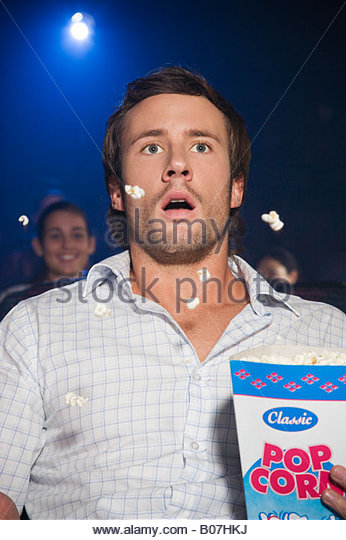 Shocked man watching a film at the cinema throwing popcorn in the air in shock - Stock Image