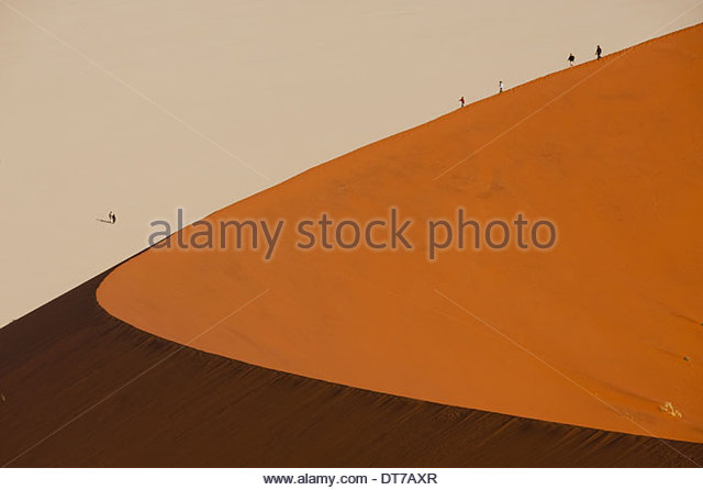 Hikers climbing up a sand dune ridge at Sossusvlei Namib-Naukluft National Park Namibia landscape wilderness - Stock Image