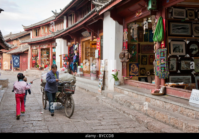 Woman with tricycle carrying goods in a narrow paved lane in Lijiang old town, Yunnan Province, China. JMH4756 - Stock Image