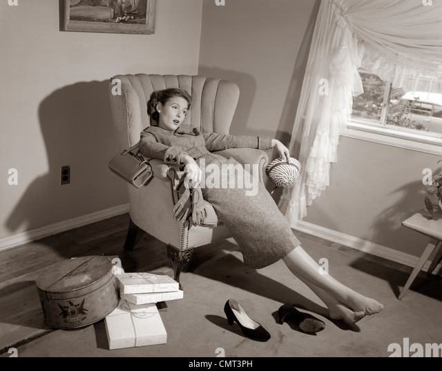 1950s EXHAUSTED FEMALE SLUMPED IN CHAIR WITH SHOES OFF AFTER SHOPPING - Stock Image