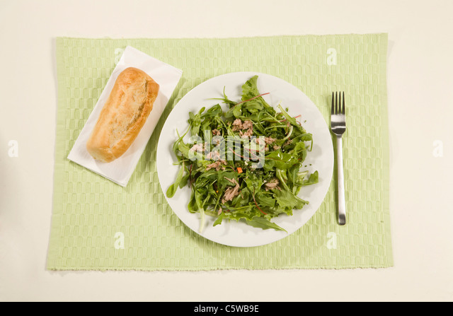 Mixed salad with tuna and bread roll, elevated view - Stock Image