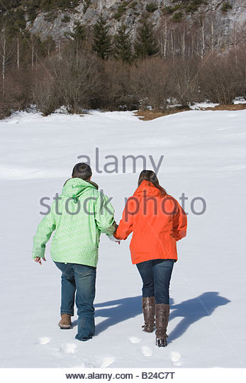 Rear view of a couple walking through snow - Stock Image