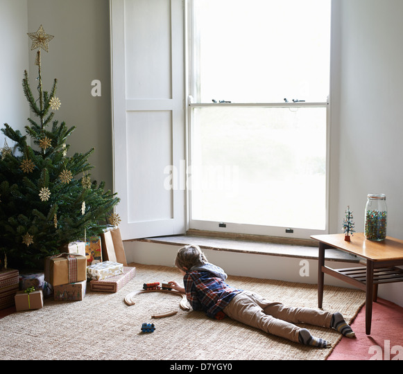 Boy playing with train by Christmas tree - Stock Image