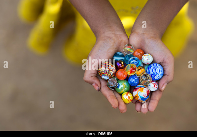Indian girls hands holding colourful marbles - Stock-Bilder