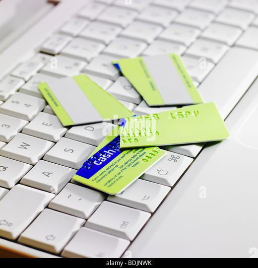 Cut up credit card on laptop keyboard. - Stock Image