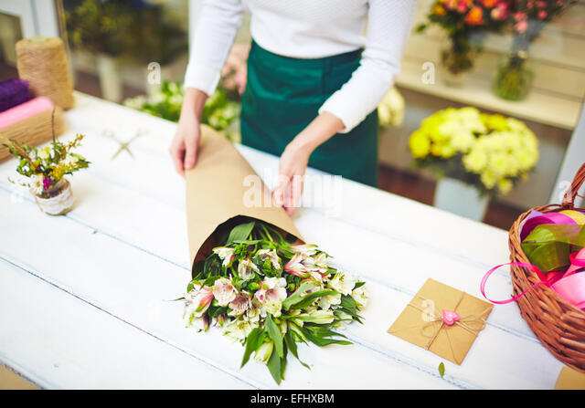 Female florist selling bouquet of amaryllises - Stock Image