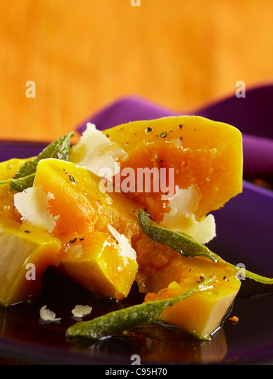 Butternut squash with sage leaves topped with shaved Parmesan - Stock Image