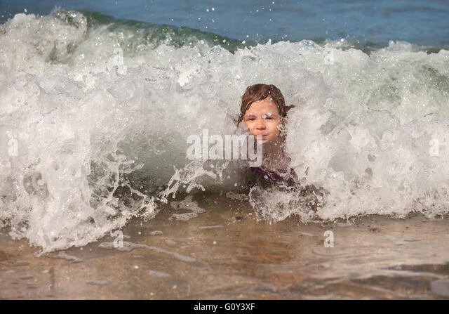 Girl playing in the surf on the beach - Stock Image