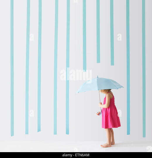 Girl with an umbrella standing under rain made of stripes - Stock Image