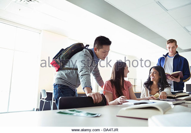 Group of students doing research in college library - Stock Image