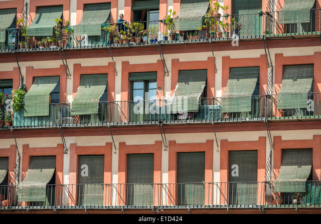 A woman surveys the square from her balcony in the Plaza de la Corredera, Cordoba, Spain. - Stock Image