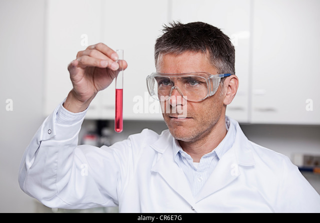 Germany, Bavaria, Munich, Scientist holding red liquid in test tube for medical research in laboratory - Stock Image