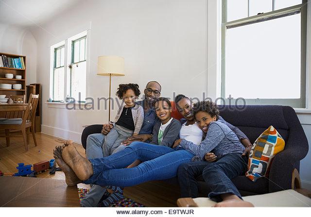 Portrait of smiling family on living room sofa - Stock-Bilder