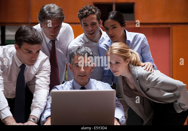 Business associates crowd around colleague looking over his shoulder at laptop computer - Stock Image