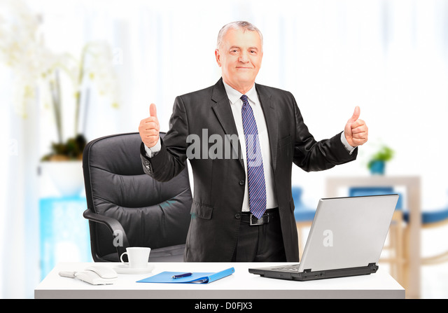 Happy mature businessman standing in his office and giving thumbs up - Stock Image