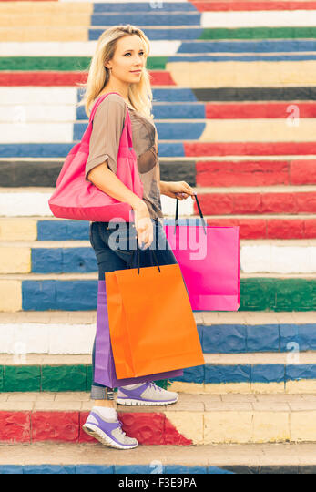 Young slim blonde woman holding shopping bags stands on the stairs and looking aside - Stock Image