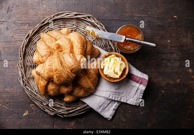 Croissants with butter and jam in wicker tray on dark wooden background - Stock Image