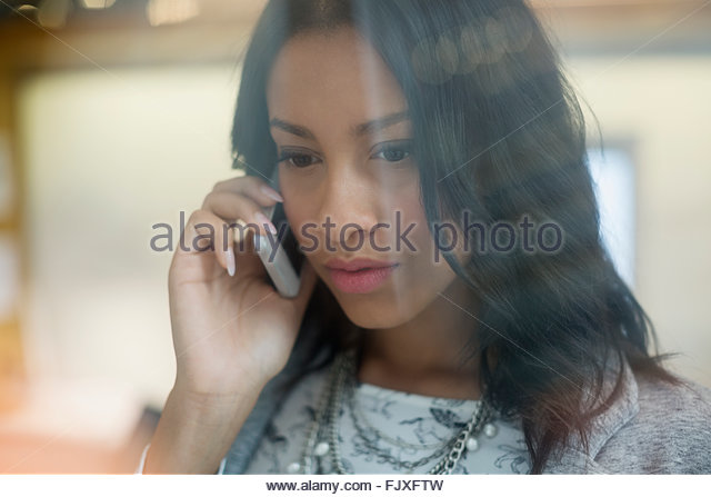 Close up serious young businesswoman talking cell phone - Stock Image