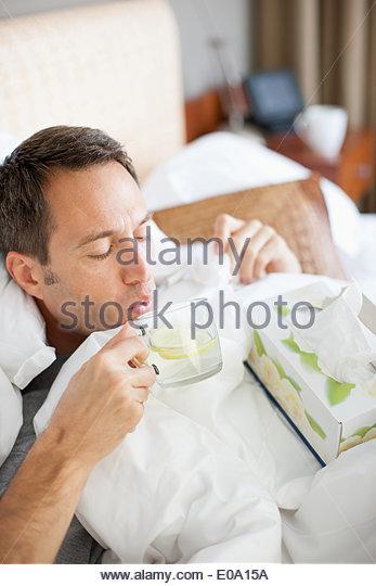 Man sick in bed drinking hot drink - Stock-Bilder